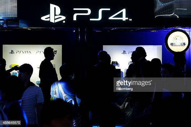 Attendees walk through the Sony Computer Entertainment Inc booth displaying the PlayStation logo at the Tokyo Game Show 2014 in Chiba Japan on...
