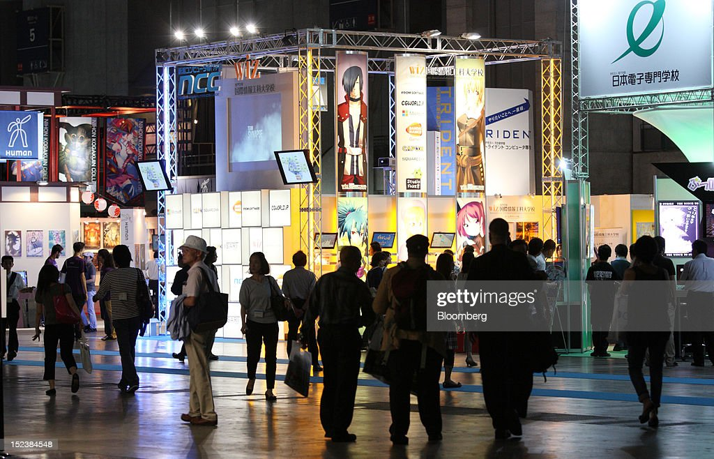 Attendees walk through the Tokyo Game Show 2012 at Makuhari Messe in Chiba, Japan, on Thursday, Sept. 20, 2012. The show will be held through Sept. 23. Photographer: Tomohiro Ohsumi/Bloomberg via Getty Images