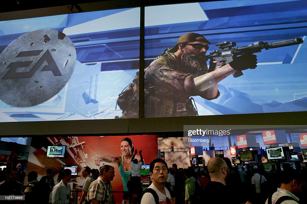 Attendees walk under a video screen for Electronic Arts Inc.'s new Medal of Honor game during the Electronic Entertainment Expo (E3) in Los Angeles, California, U.S., on Wednesday, June 16, 2010. Nintendo Co., Sony Corp., and Microsoft Corp. showed off 3-D and motion sensing capabilities for video games as the companies look to additional features to revive shrinking industry sales. Photographer: Jonathan Alcorn/Bloomberg via Getty Images