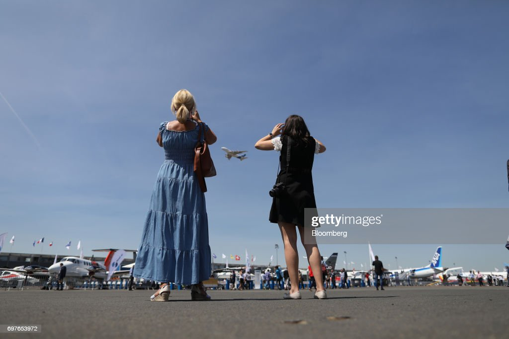 Attendees watch as an Airbus SE A380 passenger jet flies over the 53rd International Paris Air Show at Le Bourget, in Paris, France, on Monday, June 19, 2017. The show is the world's largest aviation and space industry exhibition and runs from June 19-25. Photographer: Chris Ratcliffe/Bloomberg via Getty Images