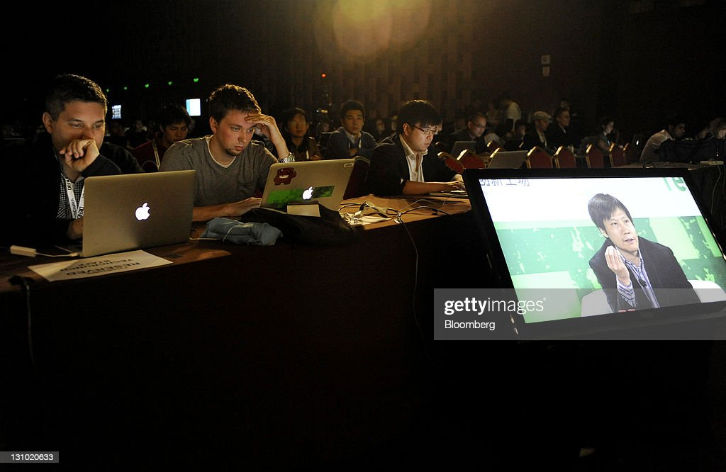 Attendees watch as Lei Jun, co-founder of Xiaomi Technology Co., displayed on a screen, speaks during the TechCrunch Disrupt Beijing conference in Beijing, China, on Tuesday, Nov. 1, 2011. Xiaomi Technology Co. aims to attract users to its first smartphone by pricing the handset at less than half that for Apple Inc.'s iPhone 4 and plans to make money through software for the device. Photographer: Keith Bedford/Bloomberg via Getty Images
