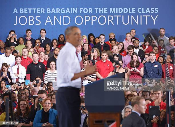 Attendees watch as US President Barack Obama speaks on the economy at North Carolina State University in Raleigh North Carolina on January 15 2014...