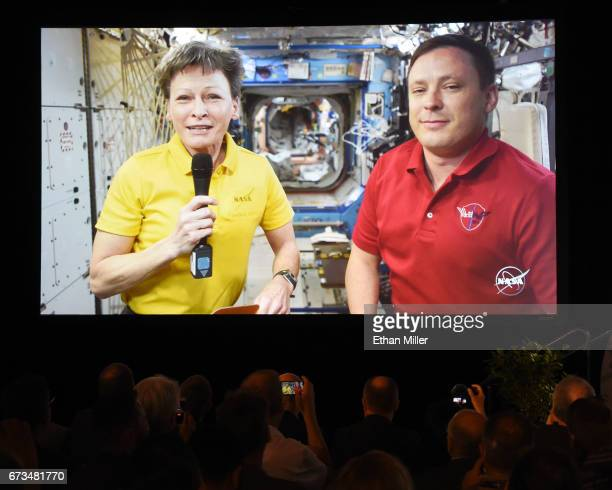 Attendees watch NASA astronauts Cmdr Peggy A Whitson and Col Jack Fischer live on screen from the International Space Station using a RED Epic Dragon...