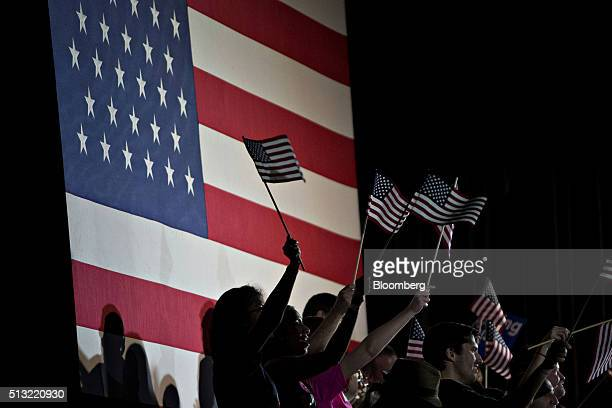 Attendees wave American flags during a Super Tuesday rally for Hillary Clinton former Secretary of State and 2016 Democratic presidential candidate...