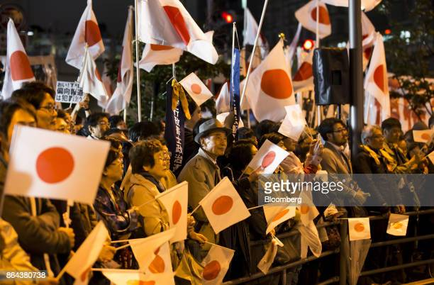 Attendees wave Japanese national flags in support of Shinzo Abe Japan's prime minister and president of the Liberal Democratic Party not pictured...