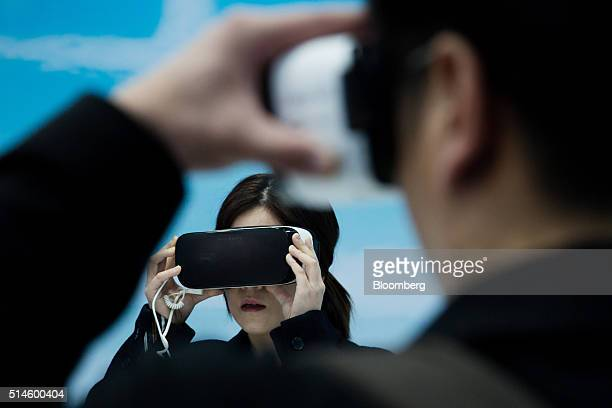 Attendees wear a Samsung Electronics Co Gear VR virtual reality headset during a media event in Seoul South Korea on Thursday March 10 2016 Samsung's...