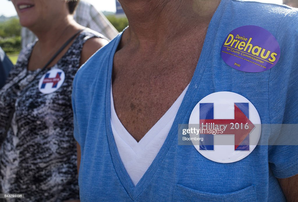 Attendees wear campaign buttons ahead of an event with Hillary Clinton, former Secretary of State and presumptive Democratic presidential nominee, not pictured, in Cincinnati, Ohio, U.S., on Monday, June 27, 2016. Clinton released a new national television ad on Sunday attacking likely Republican rival Donald Trump for his comments on the U.K's decision to leave the European Union, and later warned of the negative impact that 'bombastic' behavior can have at times of crisis. Photographer: Ty Wright/Bloomberg via Getty Images