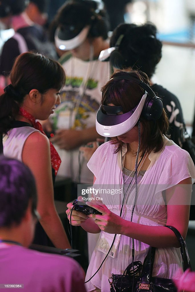 Attendees wear Sony Corp.'s HMZ-T2 3D head-mounted display as they play games on Sony Computer Entertainment Inc.'s PlayStation 3 (PS3) video game consoles during the Tokyo Game Show 2012 at Makuhari Messe on September 20, 2012 in Chiba, Japan. The annual video game expo, which is held from September 20 to 23, attracts thousands of business visitors and the general public with exhibitions of the upcoming game software and latest hardware.