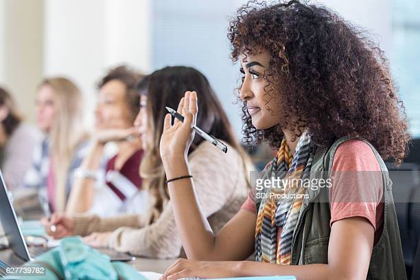 Attentive African American college student raises hand during lecture