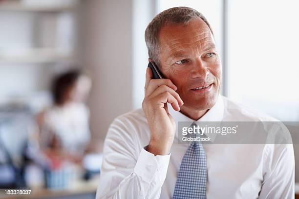 Aufmerksame Geschäftsmann am Telefon mit Kollegen im Hintergrund