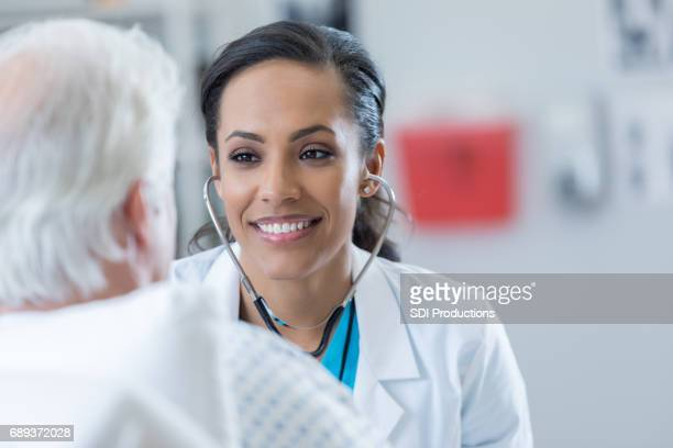 Attentive doctor listens to senior patient's lungs