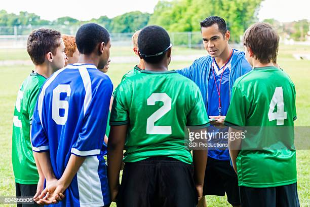 Attentive soccer players listen to coach