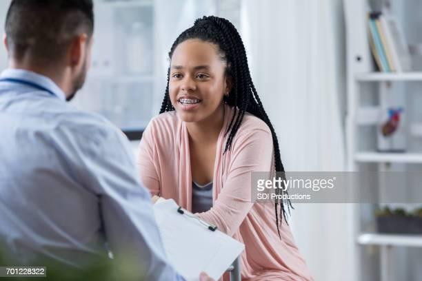 Attentive teenage girl talks with pediatrician