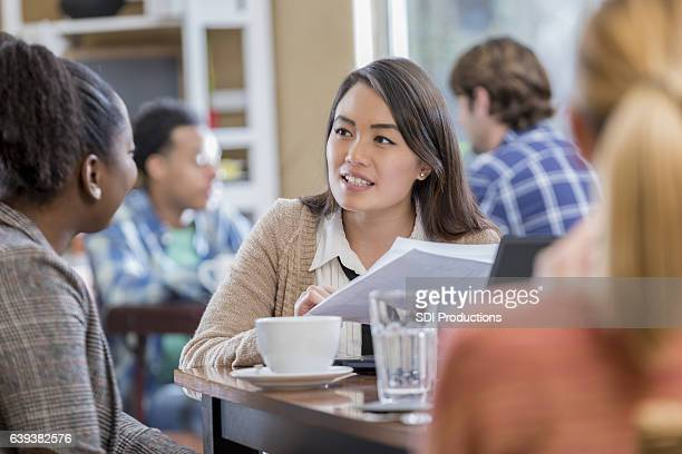 Attentive young businesswomen meet at coffee shop
