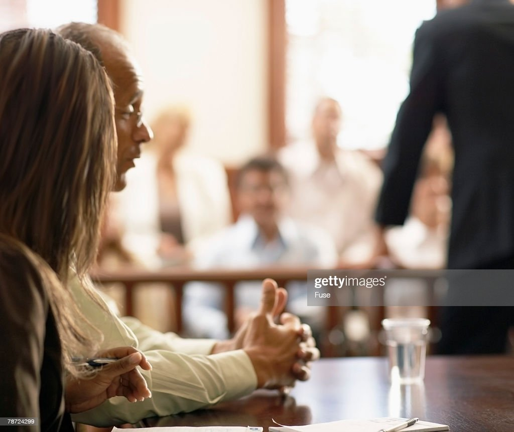 Attorney and Client Listen to Opposing Lawyer