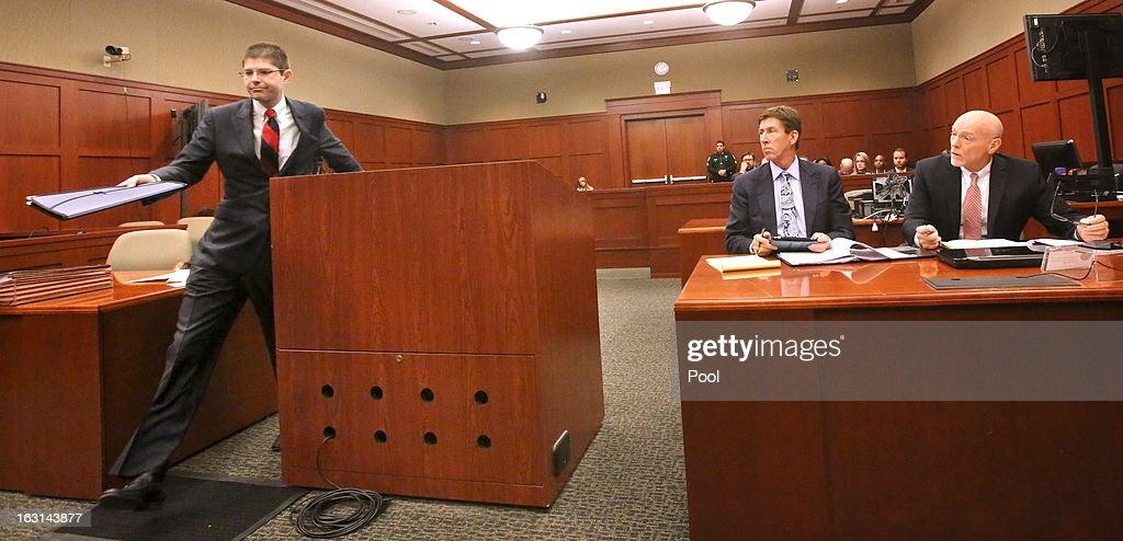 FDLE attorney David Margolis (left) hands document to the judge as George Zimmerman's lead defense attorneys, Mark O'Mara and Don West watch during a status hearing in the Trayvon Martin case, in Seminole circuit court March 5, 2013 in Sanford, Florida. The defense lawyers were reportedly looking for more access to the FBI's investigation into possible civil rights violations in the shooting of Martin.