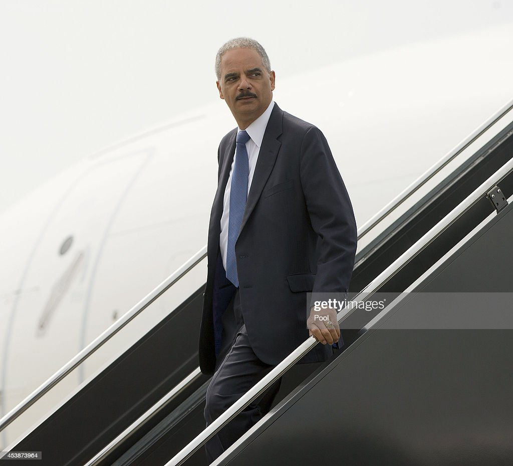 U.S. Attorney General <a gi-track='captionPersonalityLinkClicked' href=/galleries/search?phrase=Eric+Holder&family=editorial&specificpeople=1060367 ng-click='$event.stopPropagation()'>Eric Holder</a> arrives on US Military aircraft to Lambert-St. Louis International Airport August 20, 2014 in St. Louis, Missouri. Holder is traveling to Ferguson, Mo., to oversea the federal government's investigation into the shooting of 18-year-old Michael Brown by a police officer on Aug. 9th. Holder promised a 'fair and thorough' investigation into the fatal shooting of a young blackman, Michael Brown, who was unarmed when a white police officer shot him multiple times.
