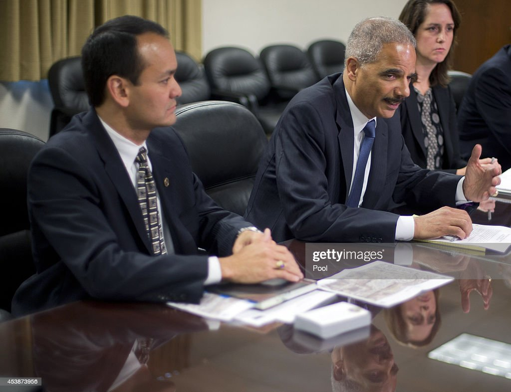 U.S. Attorney General Eric Holder, center, during his meeting with Special Agent in Charge William P. Woods, left, and Acting Assistant Attorney General for Civil Rights Molly Moran, right, at the FBI building August 20, 2014 in St. Louis, Missouri. Holder is traveling to Ferguson, Mo., to oversea the federal government's investigation into the shooting of 18-year-old Michael Brown by a police officer on Aug. 9th. Holder promised a 'fair and thorough' investigation into the fatal shooting of a young blackman, Michael Brown, who was unarmed when a white police officer shot him multiple times.
