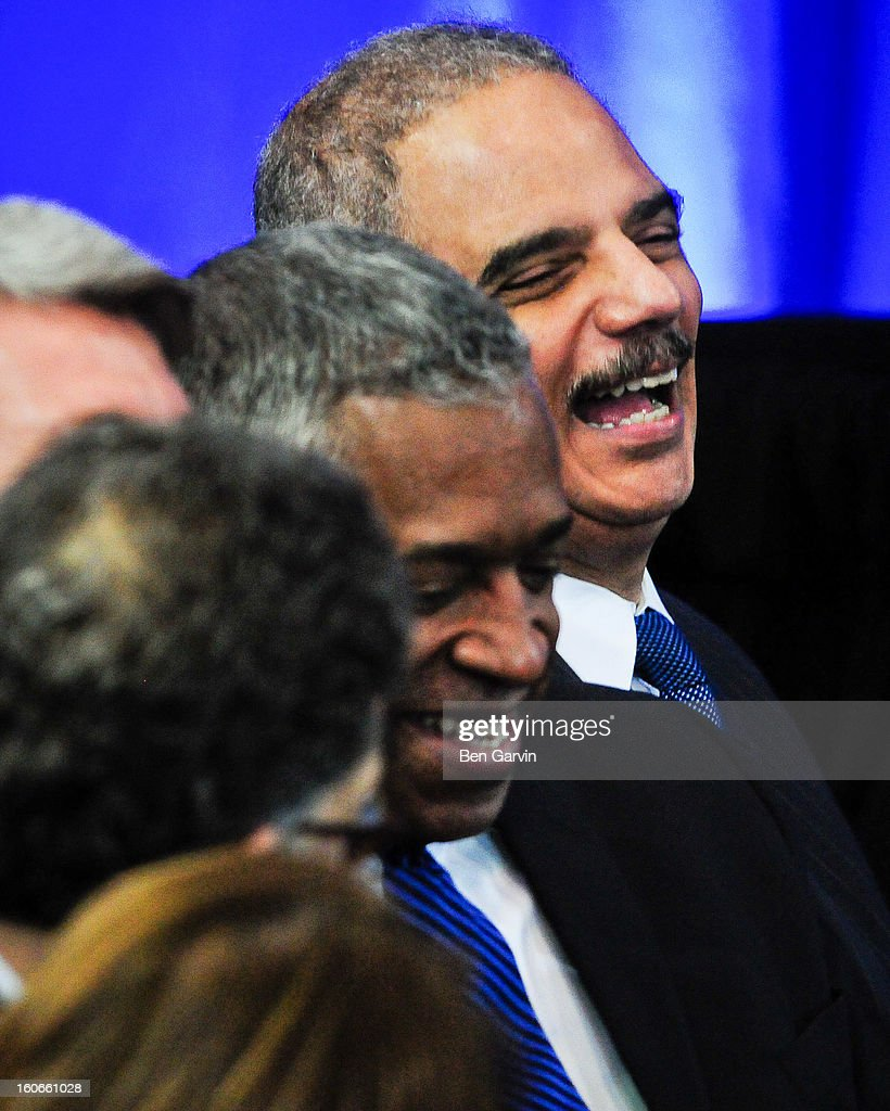 Attorney General Eric Holder laughs after U.S. President Barack Obama pretended to forget Hoder's name during an event at the Minneapolis Police Department Special Operations Center on February 4, 2013 in Minneapolis, Minnesota. President Obama is promoting a ban on assault weapons and expanded background checks on gun buyers.