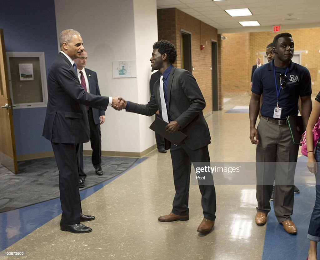 U.S. Attorney General Eric Holder, left, shakes hands with Bradley J. Rayford, 22, right, following his meeting at St. Louis Community College Florissant Valley August 20, 2014 in Ferguson, Missouri. Holder is traveling to Ferguson, Mo., to oversea the federal government's investigation into the shooting of 18-year-old Michael Brown by a police officer on Aug. 9th. Holder promised a 'fair and thorough' investigation into the fatal shooting of a young blackman, Michael Brown, who was unarmed when a white police officer shot him multiple times.