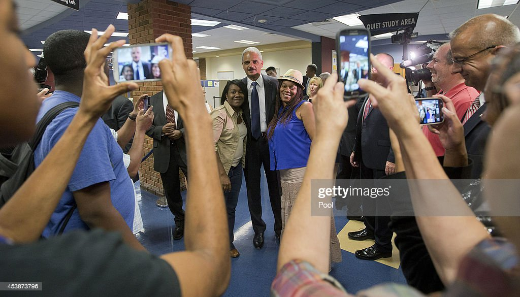 U.S. Attorney General Eric Holder (C) poses for photographs following his meeting with students at St. Louis Community College Florissant Valley August 20, 2014 in Ferguson, Missouri. Holder is traveling to Ferguson, Mo., to oversea the federal government's investigation into the shooting of 18-year-old Michael Brown by a police officer on Aug. 9th. Holder promised a 'fair and thorough' investigation into the fatal shooting of a young blackman, Michael Brown, who was unarmed when a white police officer shot him multiple times.
