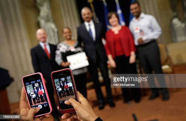 S Attorney General Eric Holder poses for photos with family members of recently naturalized US citizens following a naturalization ceremony at the US...