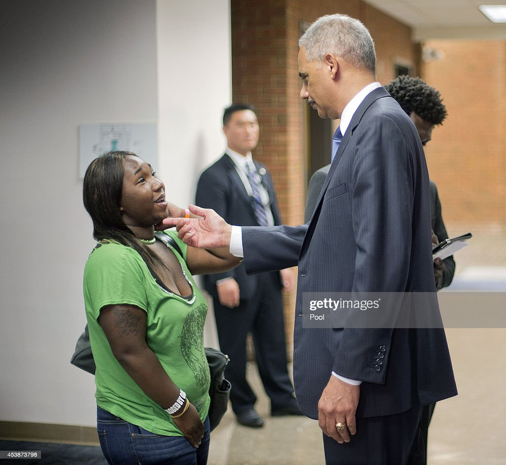 U.S. Attorney General Eric Holder, right, talks with Charnell Hurn, 20, left, a student at St. Louis Community College Florissant Valley August 20, 2014 in Ferguson, Missouri. Holder is traveling to Ferguson, Mo., to oversea the federal government's investigation into the shooting of 18-year-old Michael Brown by a police officer on Aug. 9th. Holder promised a 'fair and thorough' investigation into the fatal shooting of a young blackman, Michael Brown, who was unarmed when a white police officer shot him multiple times.