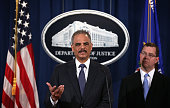 S Attorney General Eric Holder speaks as Acting Associate Attorney General Stuart Delery looks on during a news conference to make a major financial...