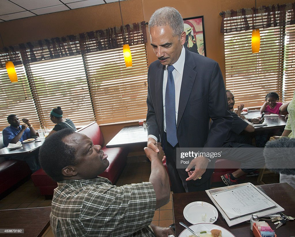 Attorney General Eric Holder stops to shake hands with a patron at Drake's Place Restaurant, before his meeting with local community leaders August 20, 2014 in Ferguson, Missouri. Holder is traveling to Ferguson, Mo., to oversea the federal government's investigation into the shooting of 18-year-old Michael Brown by a police officer on Aug. 9th. Holder promised a 'fair and thorough' investigation into the fatal shooting of a young blackman, Michael Brown, who was unarmed when a white police officer shot him multiple times.