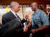 S Attorney General Eric Holder talks with Capt Ron Johnson right of the Missouri State Highway Patrol at Drake's Place RestaurantAugust 20 2014 in...