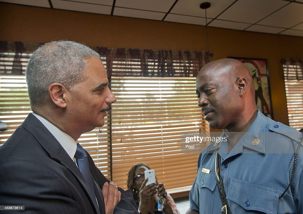 U.S. Attorney General Eric Holder (L) talks with Capt. Ron Johnson, right, of the Missouri State Highway Patrol at Drake's Place Restaurant,August 20, 2014 in Ferguson, Missouri. Holder is traveling to Ferguson, Mo., to oversea the federal government's investigation into the shooting of 18-year-old Michael Brown by a police officer on Aug. 9th. Holder promised a 'fair and thorough' investigation into the fatal shooting of a young blackman, Michael Brown, who was unarmed when a white police officer shot him multiple times.