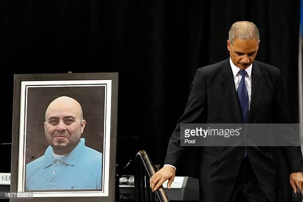 S Attorney General Eric Holder walks by a portrait of slain TSA officer Gerardo Hernandez after delivering remarks during a public memorial for...