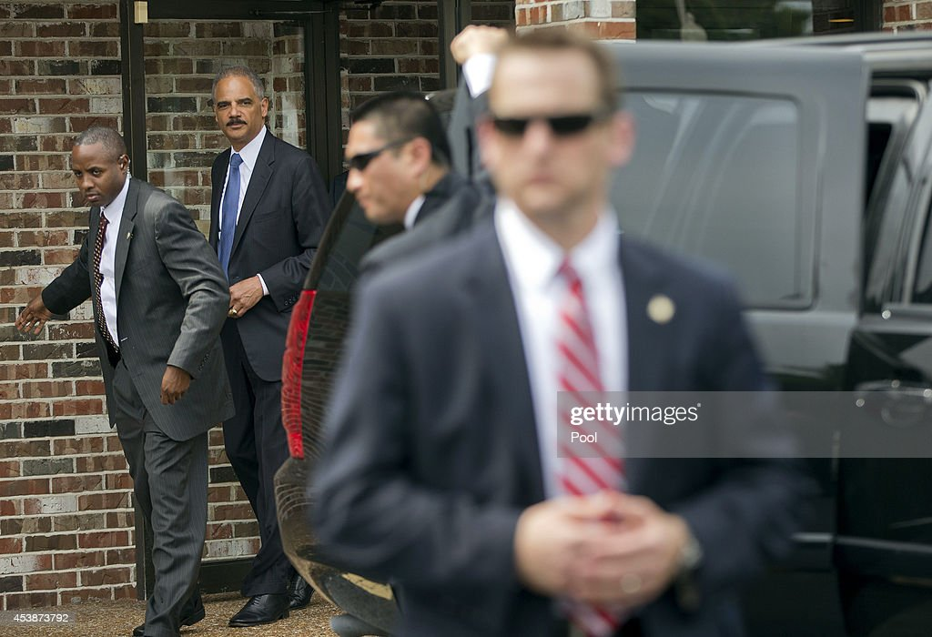 Attorney General Eric Holder (2L) walks out of Drake's Place Restaurant following his meeting with local community leaders August 20, 2014 in Ferguson, Missouri. Holder is traveling to Ferguson, Mo., to oversea the federal government's investigation into the shooting of 18-year-old Michael Brown by a police officer on Aug. 9th. Holder promised a 'fair and thorough' investigation into the fatal shooting of a young blackman, Michael Brown, who was unarmed when a white police officer shot him multiple times.