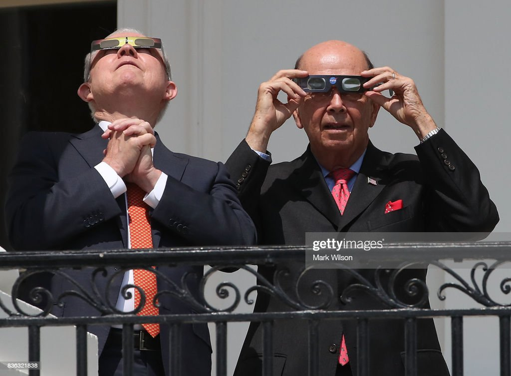 Attorney General Jeff Sessions (L) and Commerce Secretary Wilbur Ross wear special glasses to view the solar eclipse at the White House on August 21, 2017 in Washington, DC. Millions of people have flocked to areas of the U.S. that are in the 'path of totality' in order to experience a total solar eclipse.
