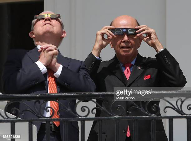 Attorney General Jeff Sessions and Commerce Secretary Wilbur Ross wear special glasses to view the solar eclipse at the White House on August 21 2017...