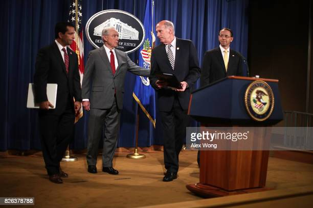 S Attorney General Jeff Sessions and Director of National Intelligence Dan Coats share a moment as Deputy Attorney General Rod Rosenstein and...