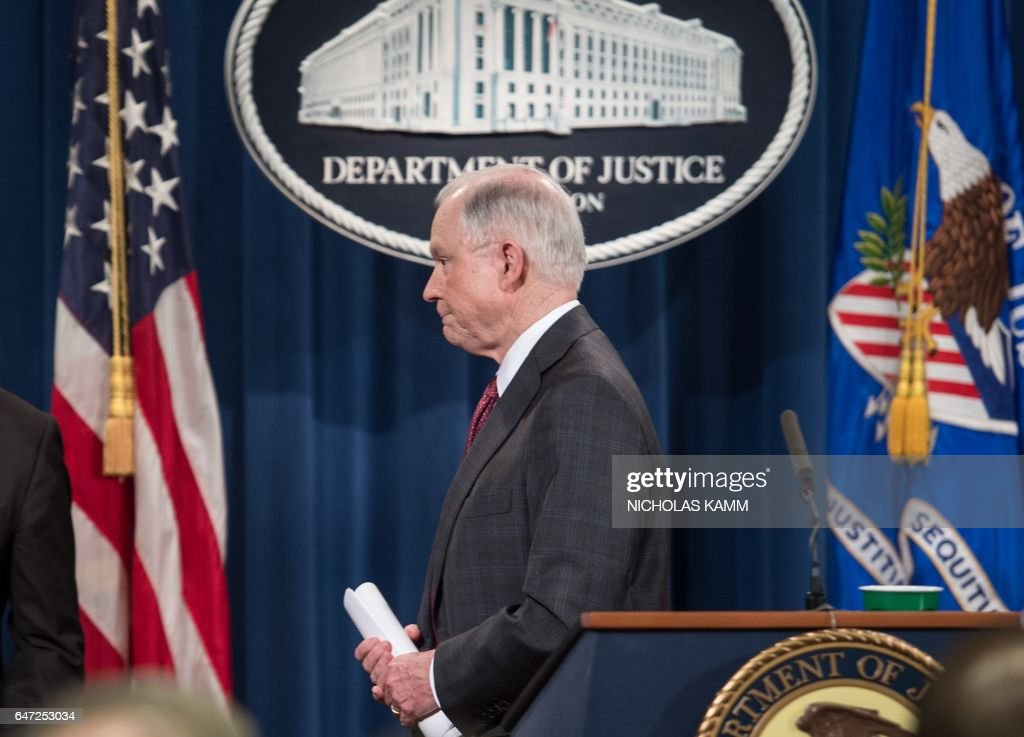 US Attorney General Jeff Sessions walks away after holding a press conference at the Justice Department in Washington, DC, on March 2, 2017. Sessions announced that he would recuse himself from any investigations into President Donald Trump's 2016 election campaign. But after receiving a strong endorsement from Trump, Sessions did not bow to pressure to step down over charges he lied to Congress about his contacts with the Russian ambassador before the election. KAMM