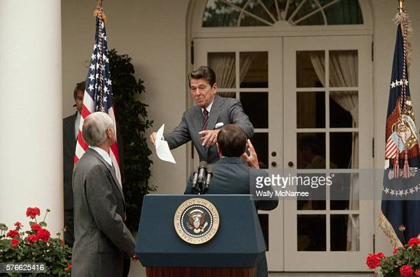 Attorney General William French Smith left and Transportation Secretary Andrew Lewis right flank President Ronald Reagan as he leaves a news...