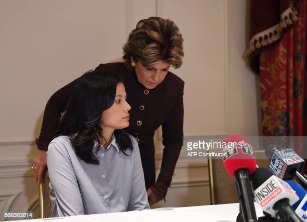 Attorney Gloria Allred pulls close a chair for new alleged victim of film producer Harvey Weinstein actor and model Natassia Malthe during a press...