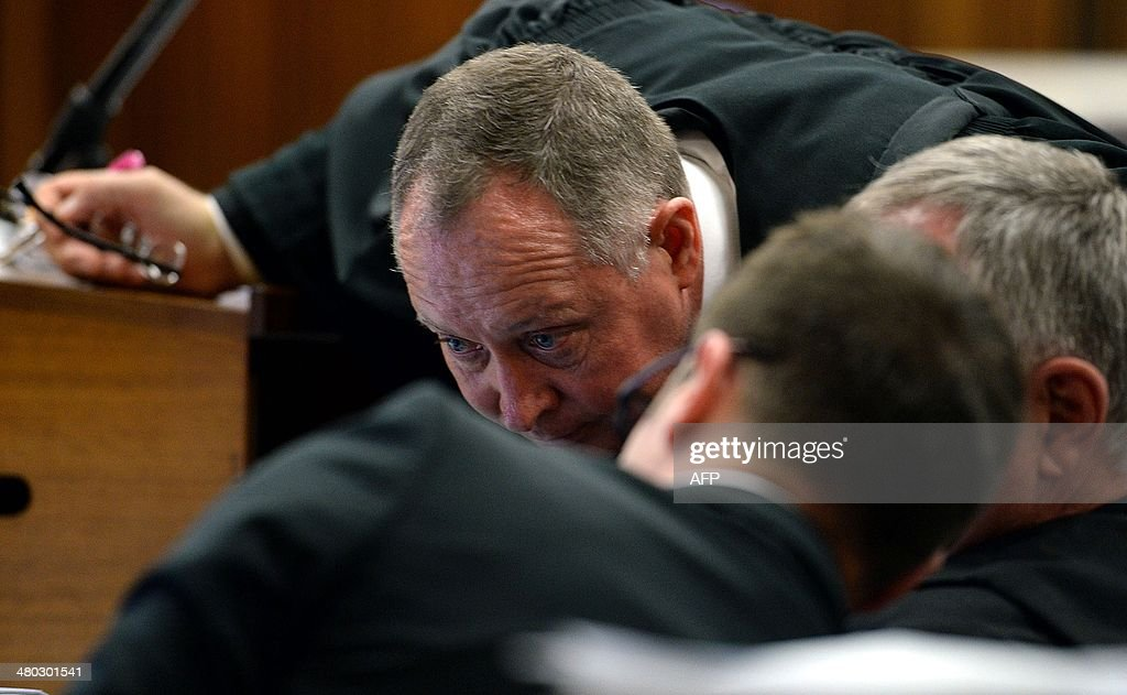 Attorney Kenny Oldwage (C) listens to lawyer Barry Roux during the trial of South African Paralympic athlete Oscar Pistorius on March 24, 2014 in Pretoria. Oscar Pistorius's murder trial entered its fourth week with more testimony on gunshots and a woman's terrified screams on the night the star Paralympian shot dead his glamorous girlfriend. AFP PHOTO / POOL Chris Collingridge