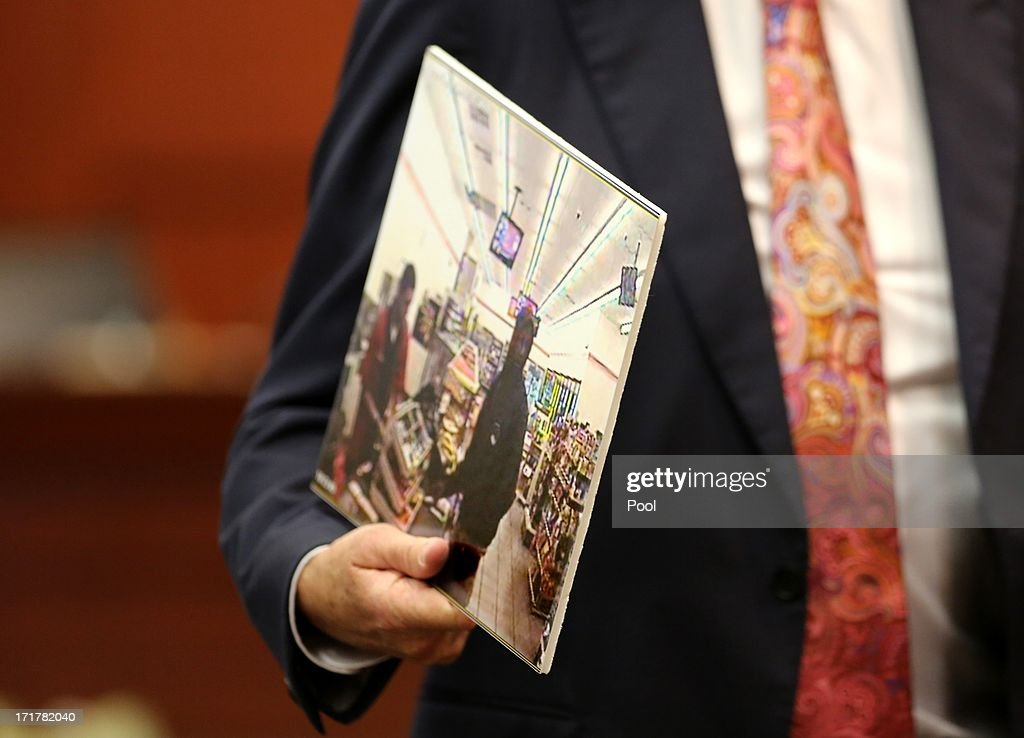 Attorney Mark O'Mara, defense counsel for George Zimmerman, holds an evidence photo of Trayvon Martin while questioning a state witness, during the 15th day of Zimmerman's murder trial in Seminole circuit court June 28, 2013 in Sanford, Florida. Zimmerman is charged with second-degree murder for the February 2012 shooting death of 17-year-old Trayvon Martin.
