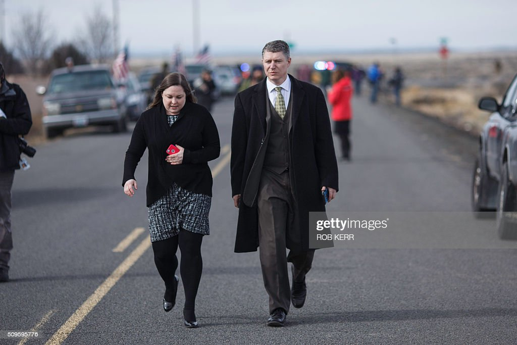 Attorney Mike Arnold, who is representing organizer Ammon Bundy, and a colleague walk along a road lined with media and protestors at the Malheur Wildlife Refuge Headquarters near Burns, Oregon, on February 11, 2016. The FBI surrounded the last protesters holed up at a federal wildlife refuge in Oregon amid reports they will surrender on Thursday, suggesting the weeks-long armed siege is approaching a climax. / AFP / Rob Kerr
