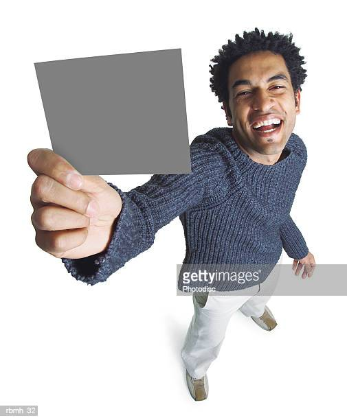attractive african american man wears khaki pants grey sweater holds blank sign smiles at camera