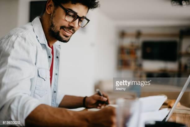 Attraktive Afrikaner Mann schreibt in notebook