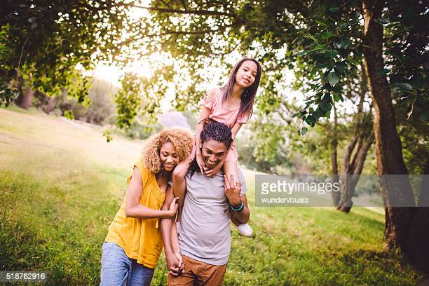 Attractive African-American family having a stroll together in b