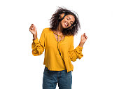 Attractive african-american young woman listening to music with headphones and dancing on white wall background. Girl in yellow fall top. Studio shot. Music concept.