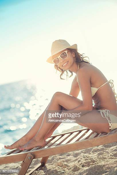 Attractive and Smiling Young Woman with Hat Sunbathing on Beach