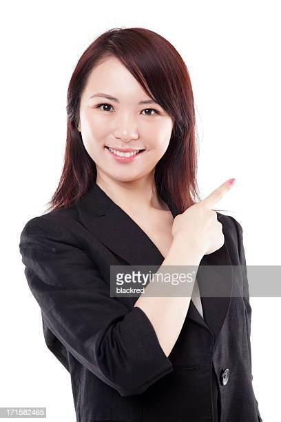 アジアのビジネスウーマンの魅力的な笑顔を指す白い背景