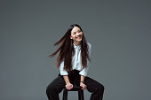 attractive asian girl sitting on chair and smiling at camera isolated on grey