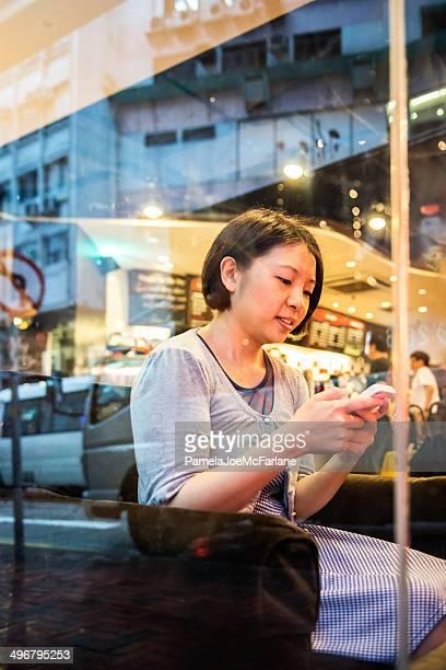 魅力的なアジアの女性のためのリラクゼーションで、コーヒーショップ